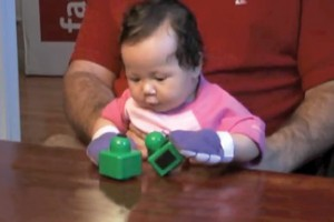 """In a new study published in the journal Developmental Science, researchers from Peabody and the Kennedy Krieger Institute found that early motor experiences can shape infants' preference for objects and faces. In the photo below, taken from video of project participants, an infant using """"sticky mittens"""" is shown manipulating toys. This kind of early motor development was shown to increase interest in faces, suggesting that it advances social skills."""