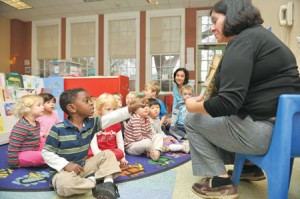 Ginette Cambronero's preschool class of 3- and 4-year-olds responds to questions she asks during group reading time. Cambronero teaches at the Vanderbilt Child Care Center.