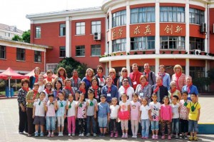 The cohort gathered for a photo in front of a Shanghai school with students.