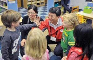 Guoming Long receives a high five from a Susan Gray School student during a tour of the school for ELLE participants as Gao Guangtang watches.