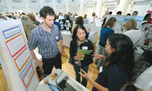 Avi Richman (left) and Hada Flores (right, speaking) with Xiu Cravens, associate dean of international affairs, at a September poster event at the Wyatt Center highlighting students' summer internship experiences. Richman and Flores are students in the master's program in International Education Policy Management, for those who plan to study education and its effect on social and economic development in learning environments around the world.