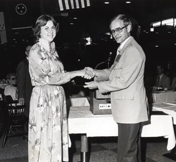 Upon graduation in 1979, Fran Schwaiger Presley received the Engineering Science award from Howard Hartman, dean of the School of Engineering. Registrar Eleanor T. (Totty) Hughes (in background at left) filled in for Presley's mother during Commencement activities.